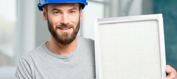 man in hard hat holding HEPA filter