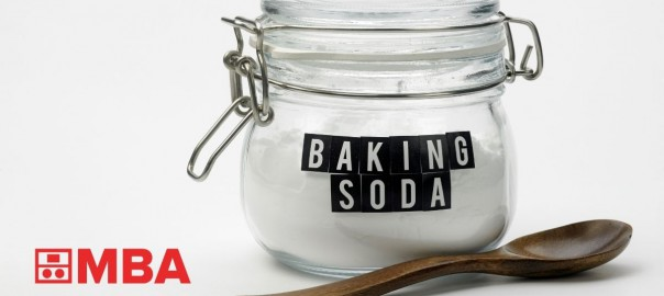 jar of baking soda and wooden spoon